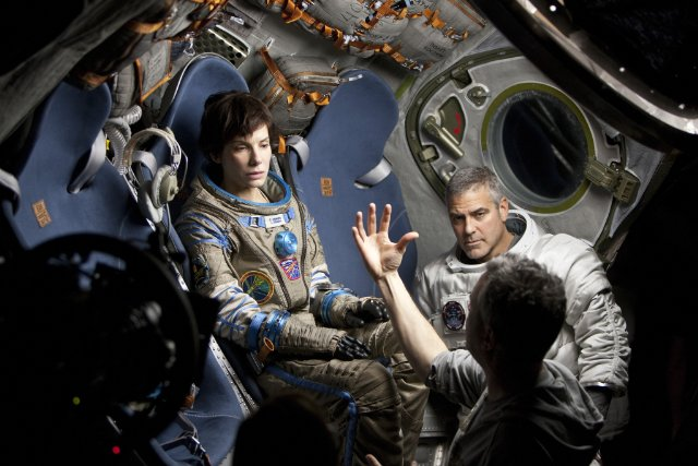 "Sandra Bullock and George Clooney speak with director Alfonso Cuaron while making ""Gravity."""